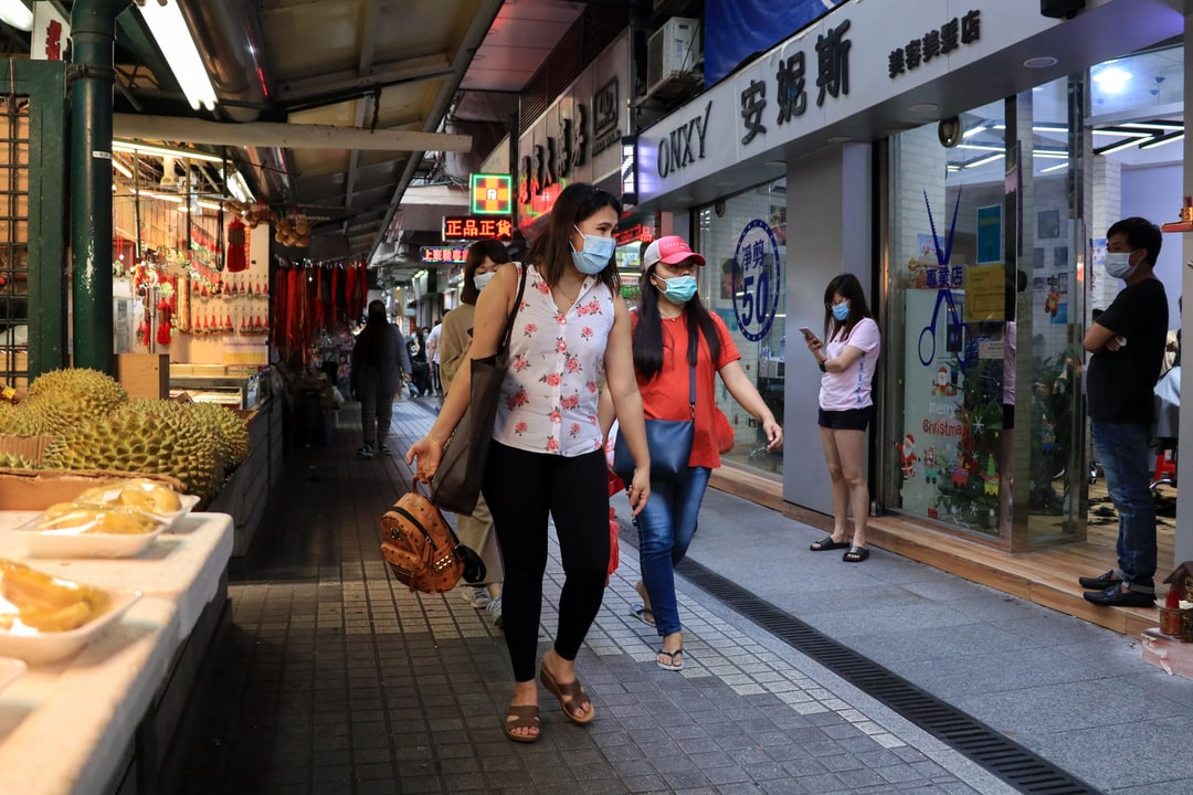 People walk in one of Macau's more popular market places wearing facemasks