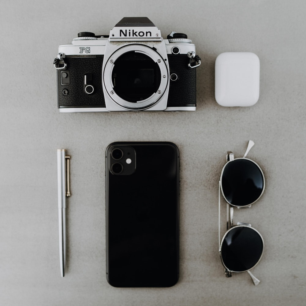 black and silver canon dslr camera beside white iphone 4 and black iphone 5