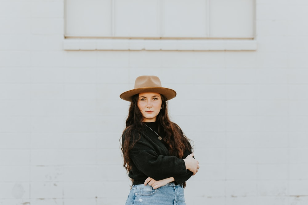 woman in black long sleeve shirt and blue denim jeans wearing brown hat