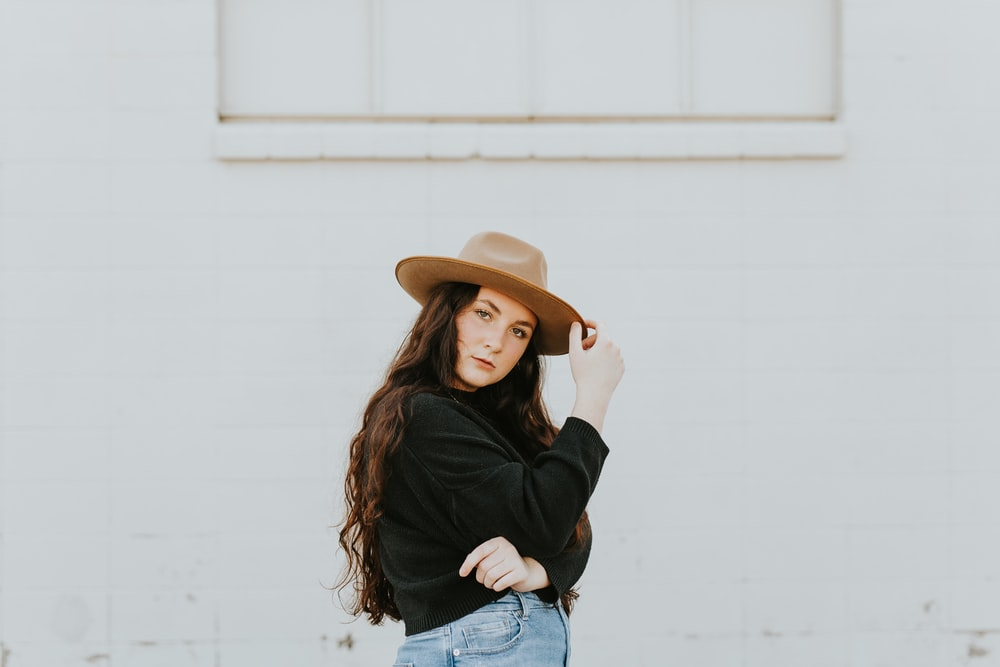 woman in black long sleeve shirt and blue denim jeans wearing brown cowboy hat