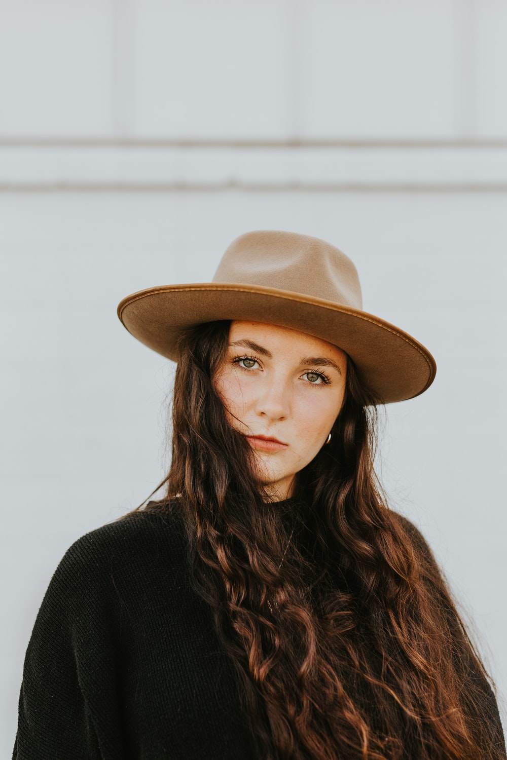 woman in black shirt wearing brown fedora hat