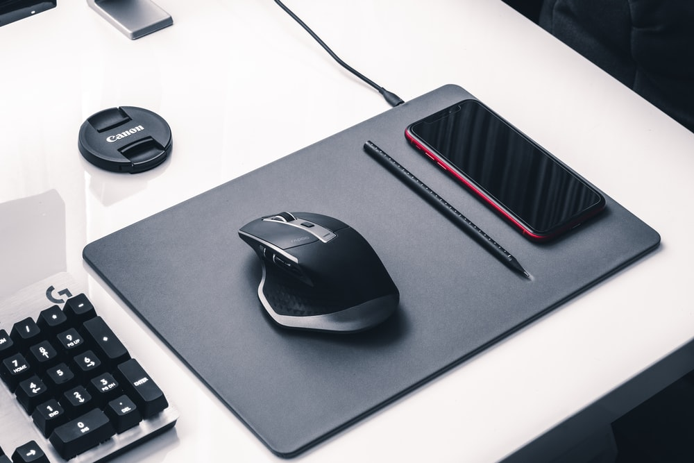 black and gray corded computer mouse on black mouse pad
