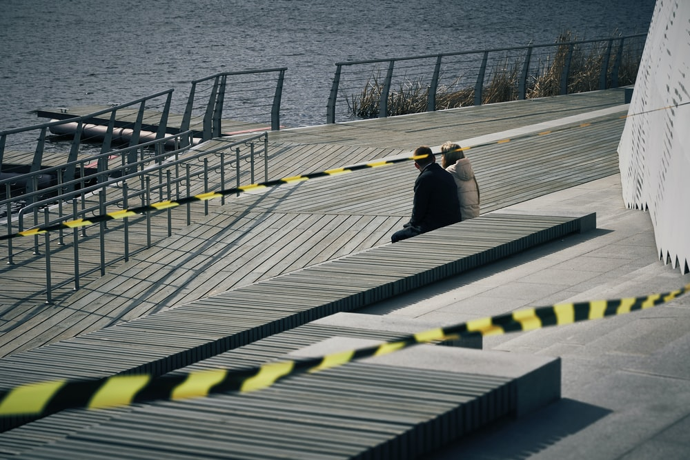 man and woman walking on gray wooden dock during daytime