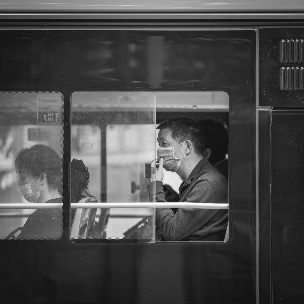 grayscale photo of man in jacket sitting on train