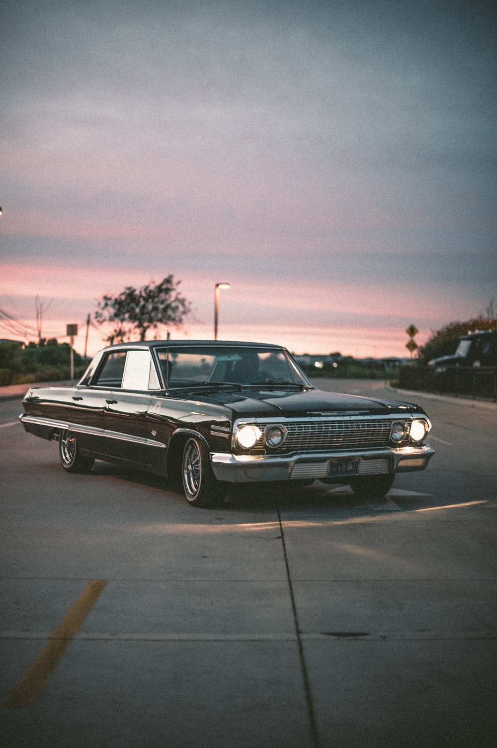 black muscle car on road during sunset