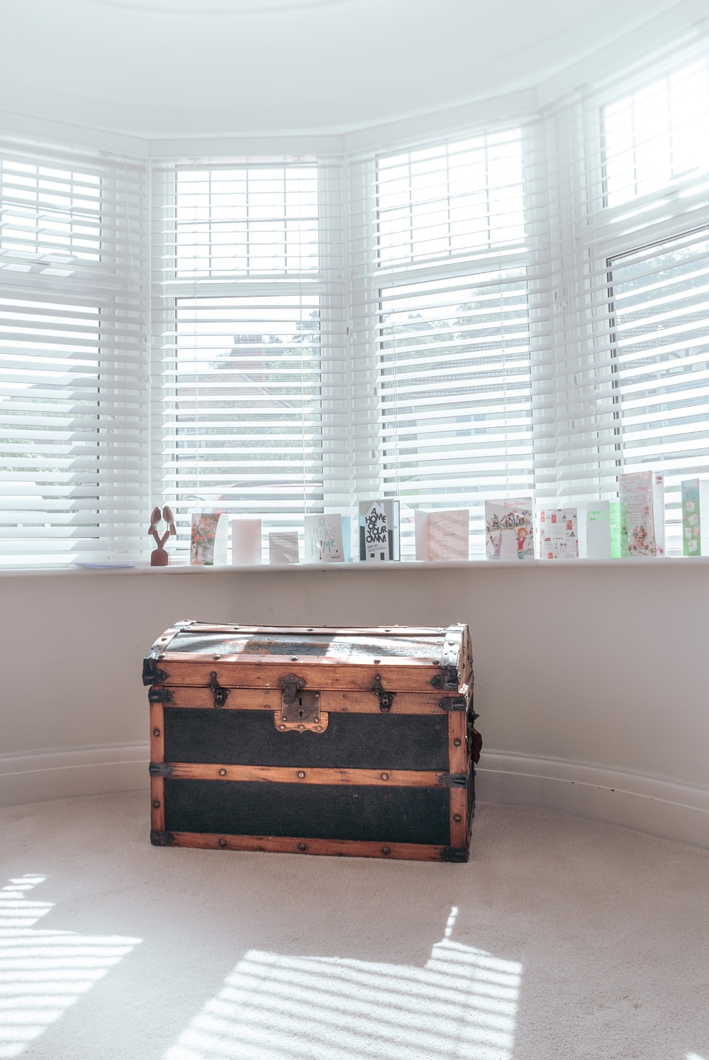 brown wooden chest box near white window blinds