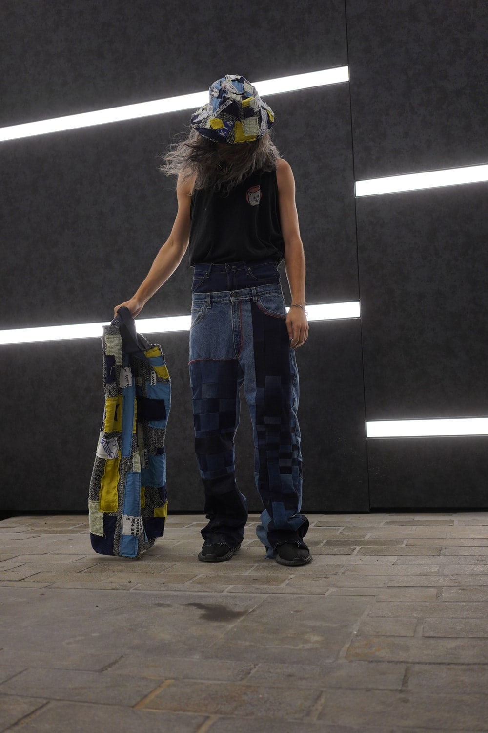 woman in black tank top and blue denim jeans standing beside black wall