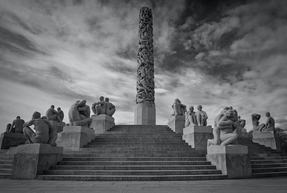 grayscale photo of people sitting on concrete stairs