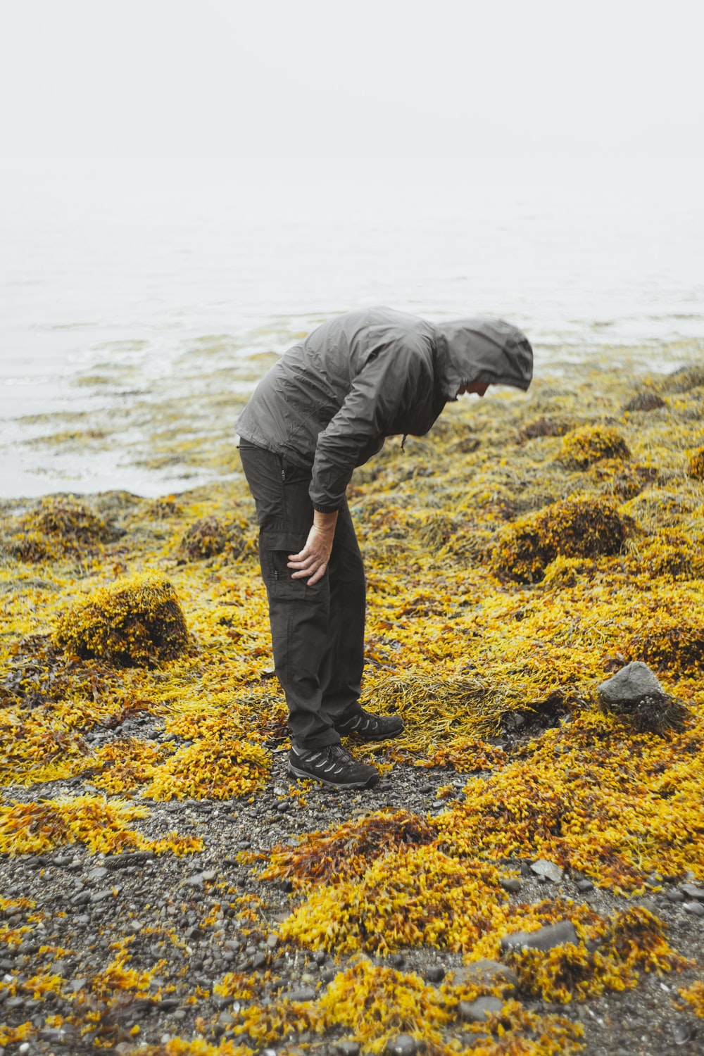 man in black jacket and black pants standing on rock near body of water during daytime