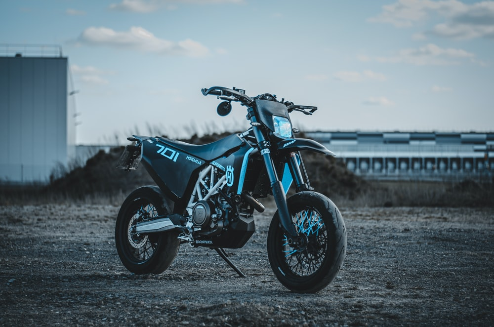 blue and black motorcycle on brown field during daytime