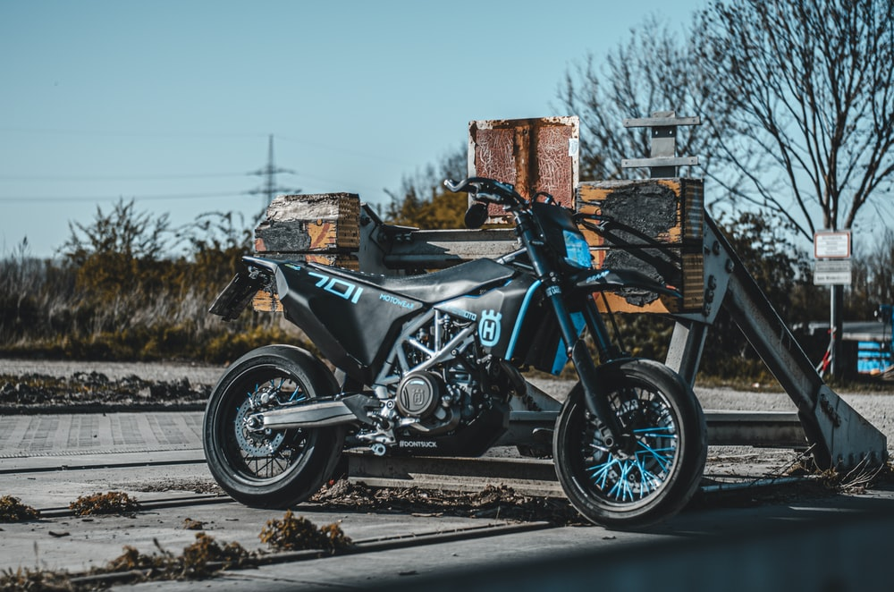 black and blue motorcycle parked on gray concrete road during daytime