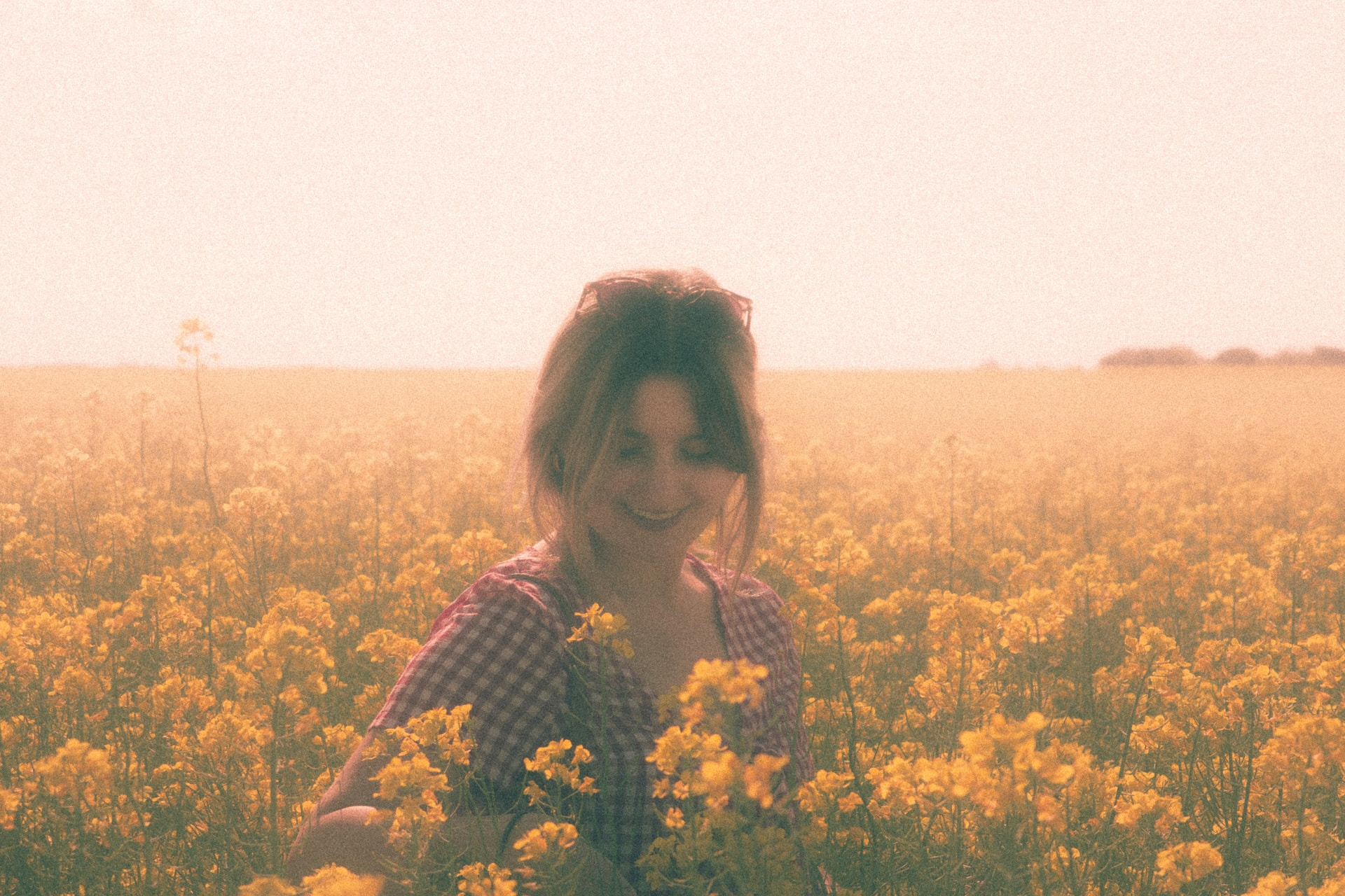 woman in black and white long sleeve shirt standing on yellow flower field during daytime