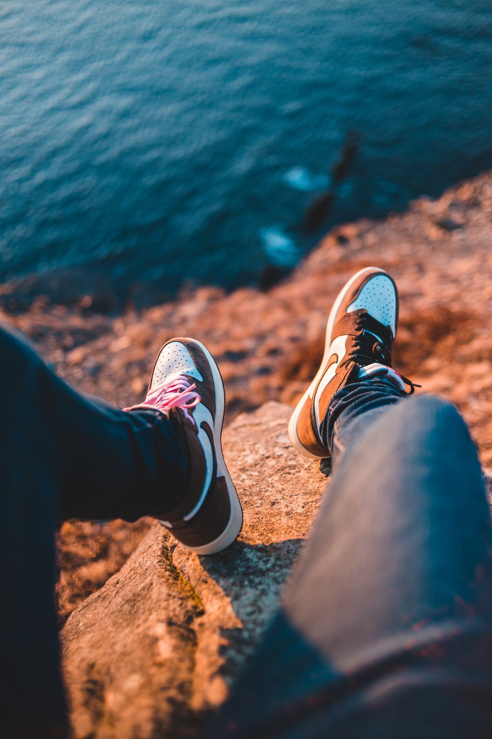 person in black pants and brown and white sneakers sitting on brown rock near body of near near near near