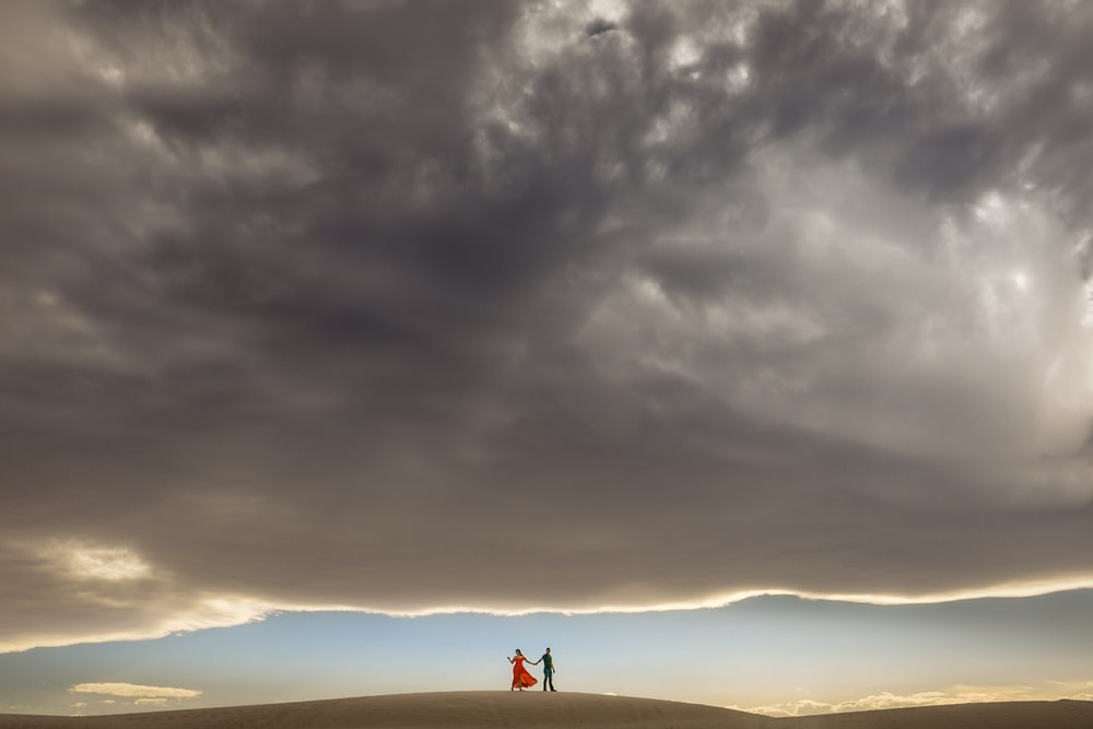 silhouette of person standing on top of hill under cloudy sky during daytime
