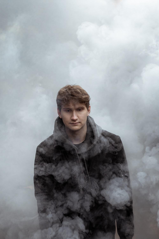 man in black hoodie standing under white clouds