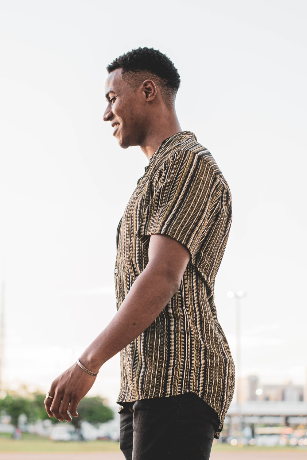 man in black and white stripe shirt standing during daytime