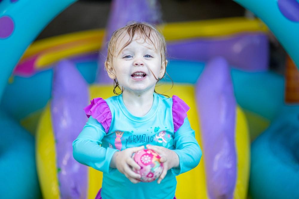 girl in teal long sleeve shirt smiling