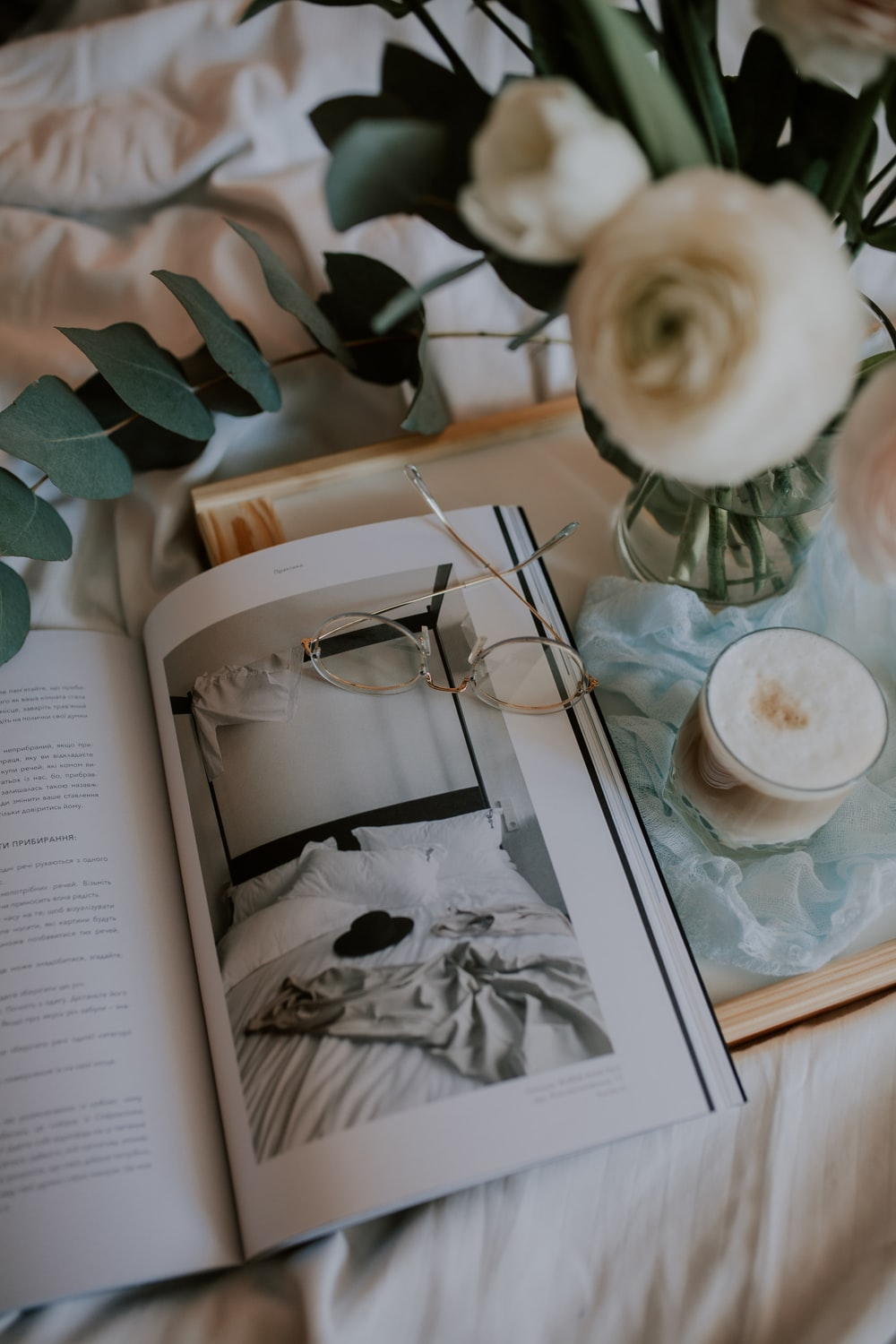 white ceramic teacup on white ceramic saucer on book page