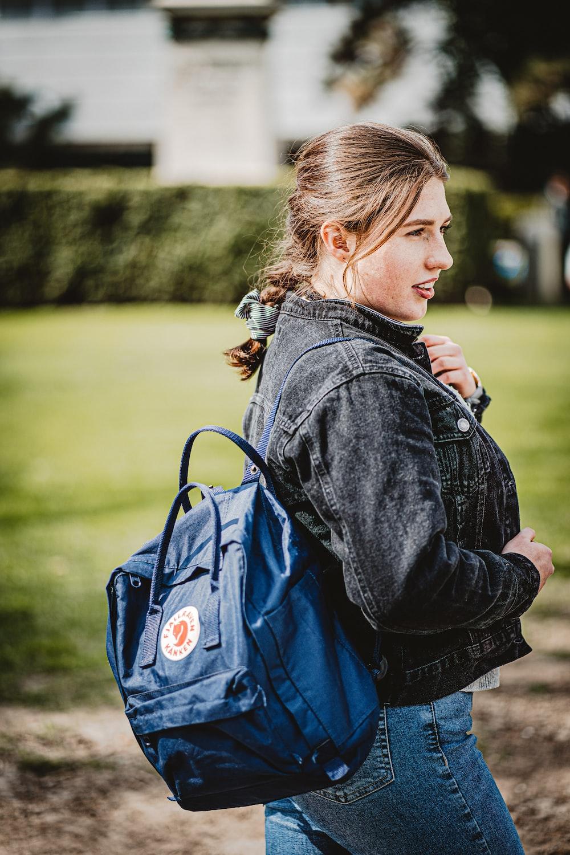 girl in blue denim jacket with blue backpack