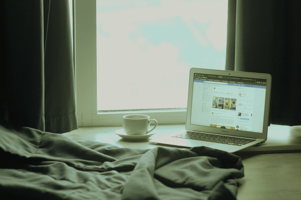 white laptop computer on bed