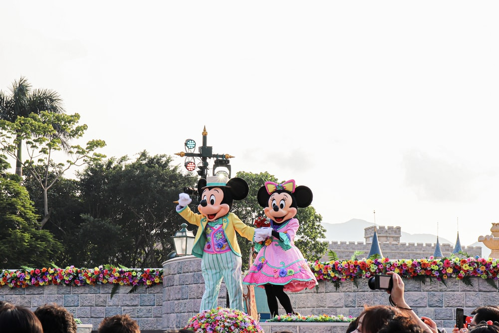 people in minnie mouse costume standing on the street during daytime