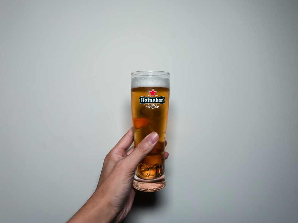 person holding clear drinking glass with beer