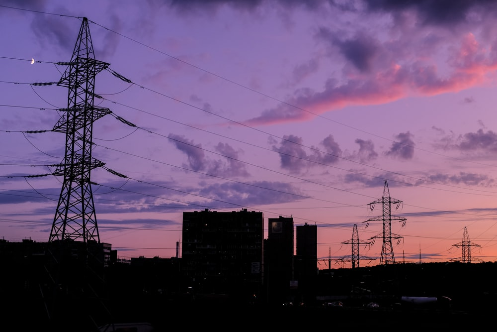 silhouette of buildings under cloudy sky during sunset