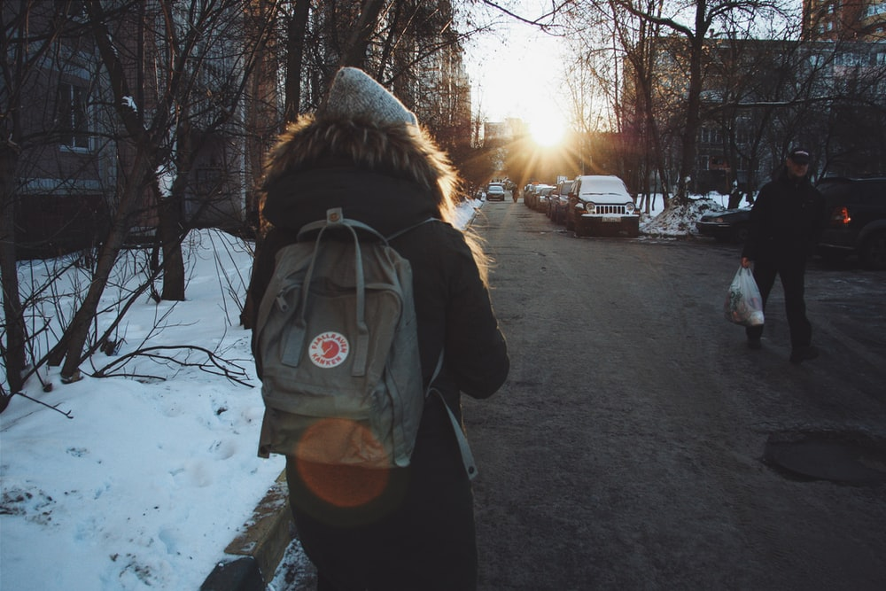 woman in black jacket and brown backpack standing on road during daytime