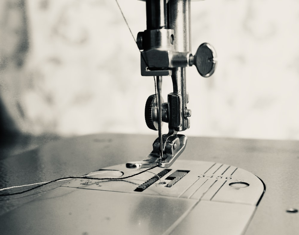 gray scale photo of sewing machine
