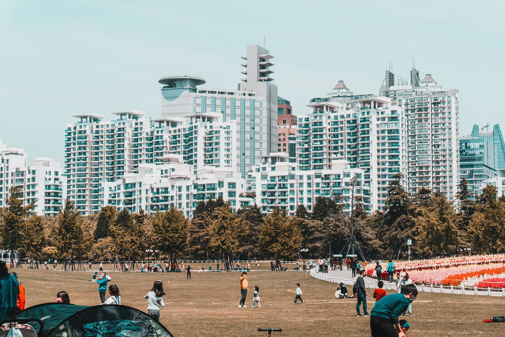 people walking on park near high rise buildings during daytime
