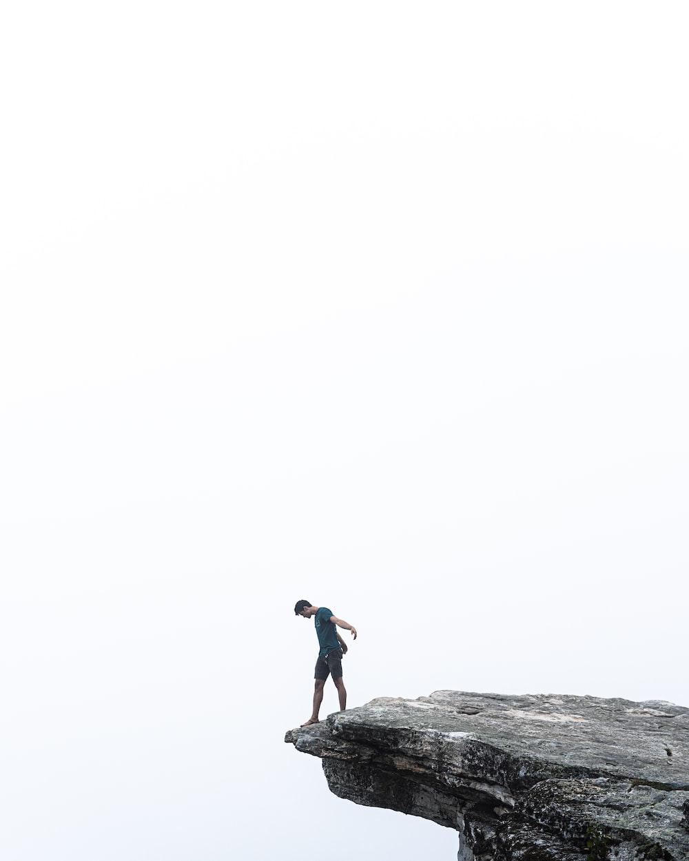 man in black shirt standing on rock
