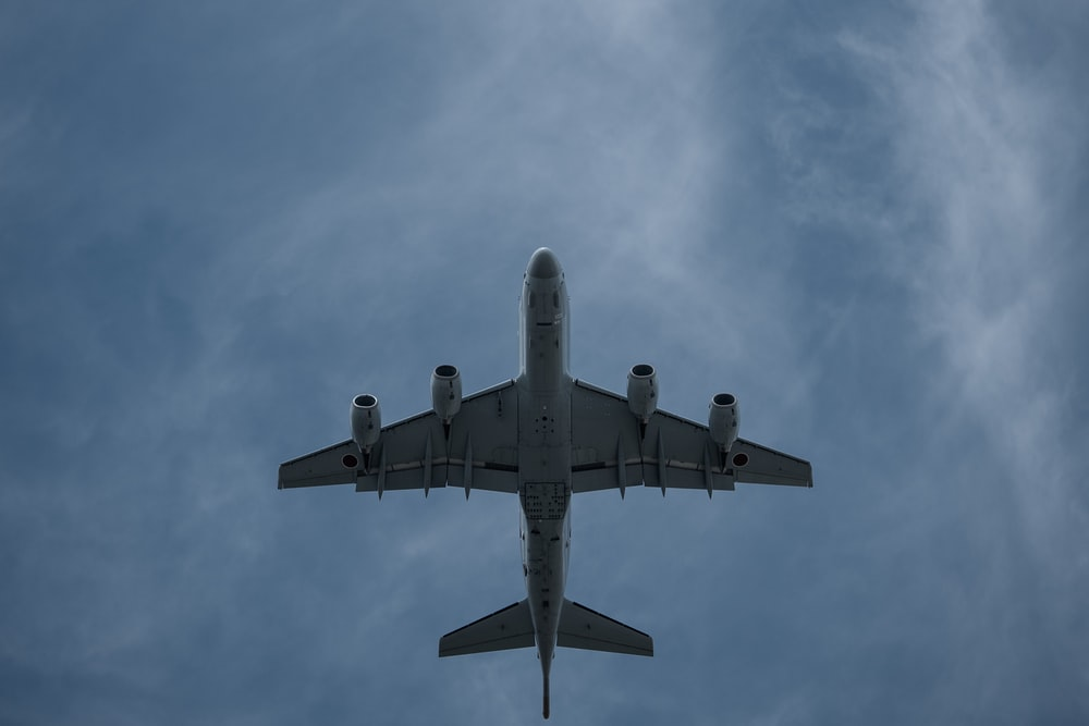 gray airplane under white clouds during daytime