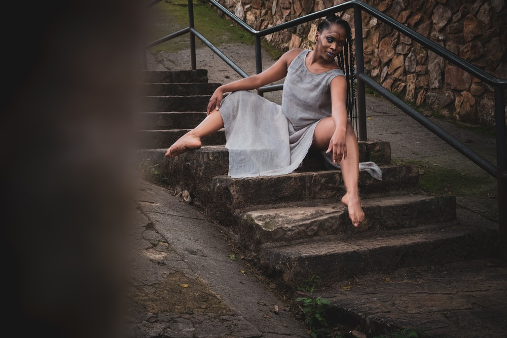 woman in white dress sitting on stairs