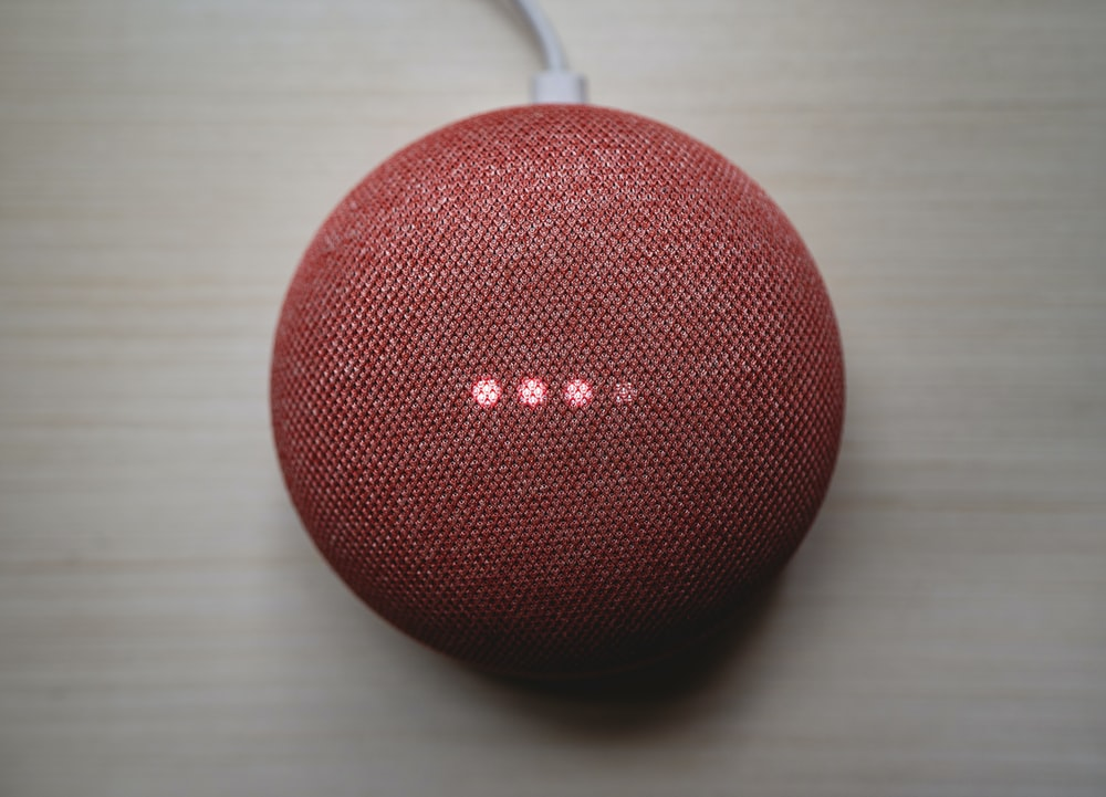 red round portable speaker on brown wooden table