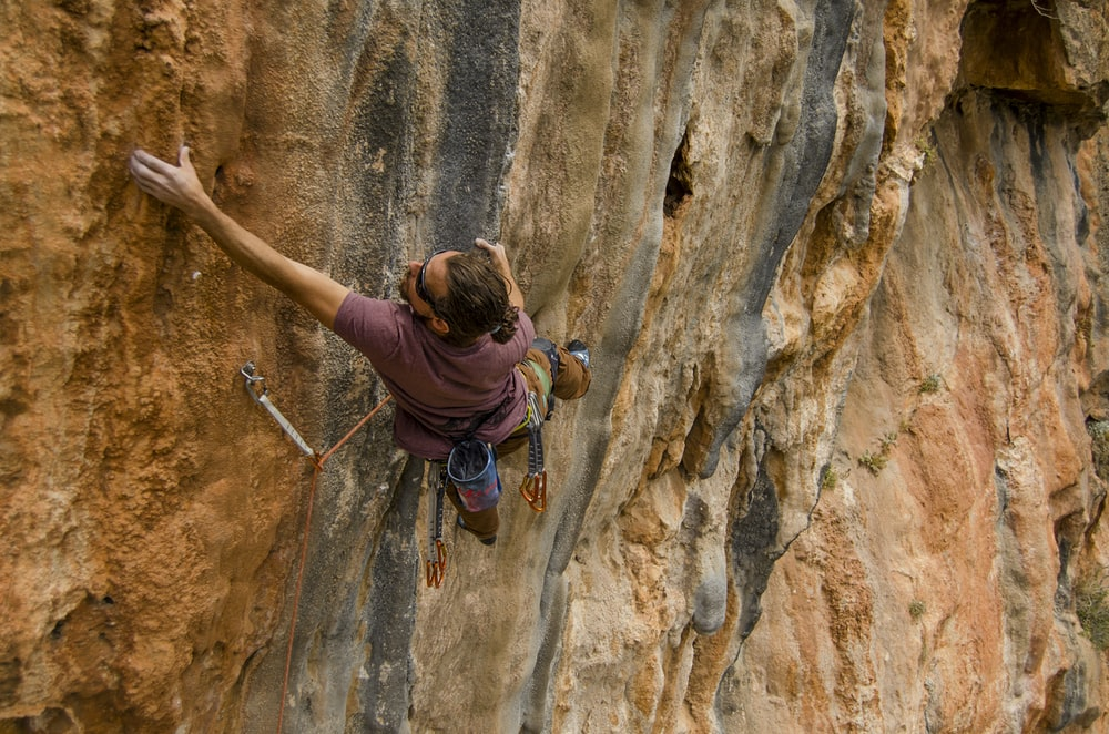 woman in purple long sleeve shirt climbing on brown rock during daytime