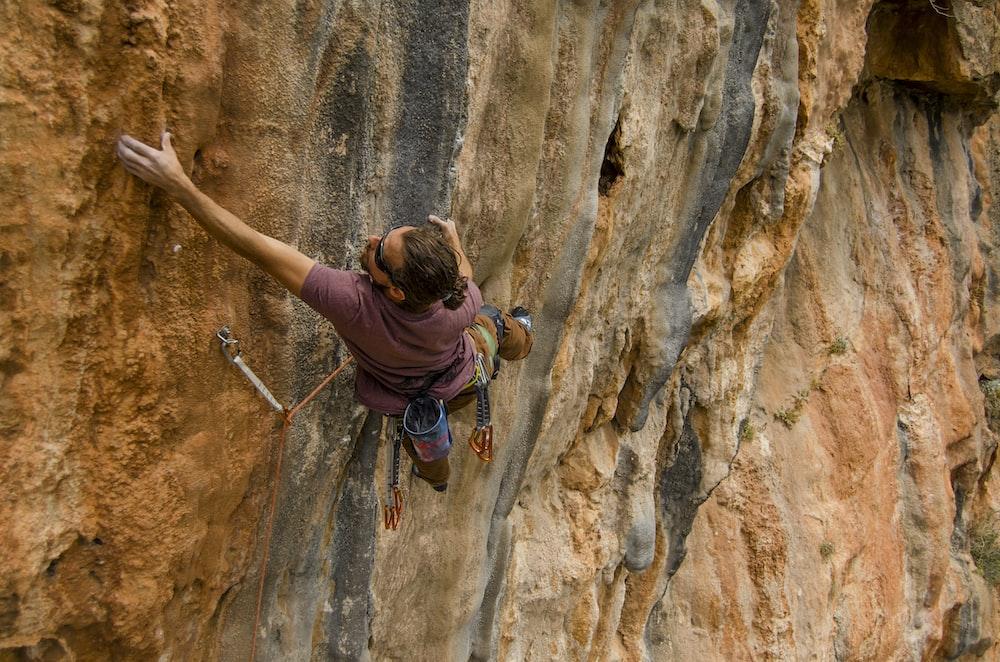 woman in purple long sleeve shirt climbing on brown rock during daytime
