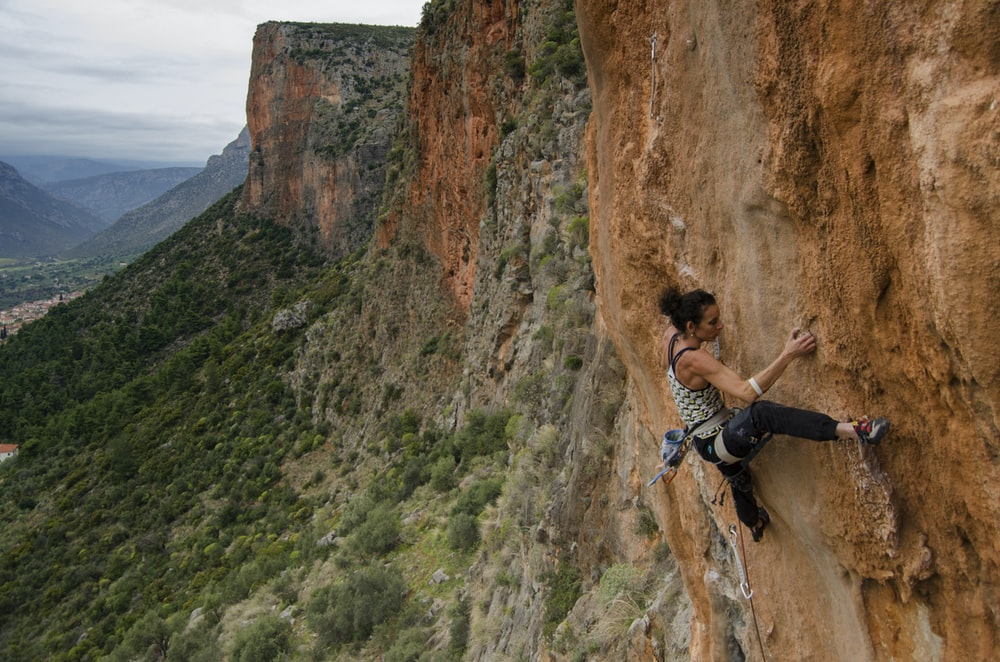 woman in black tank top climbing on brown rocky mountain during daytime