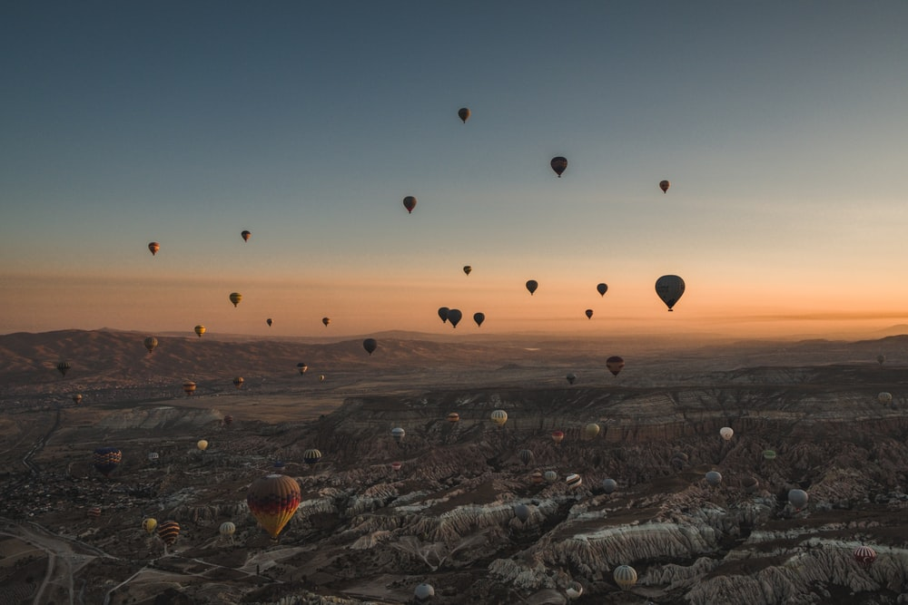 hot air balloons flying over the city during sunset