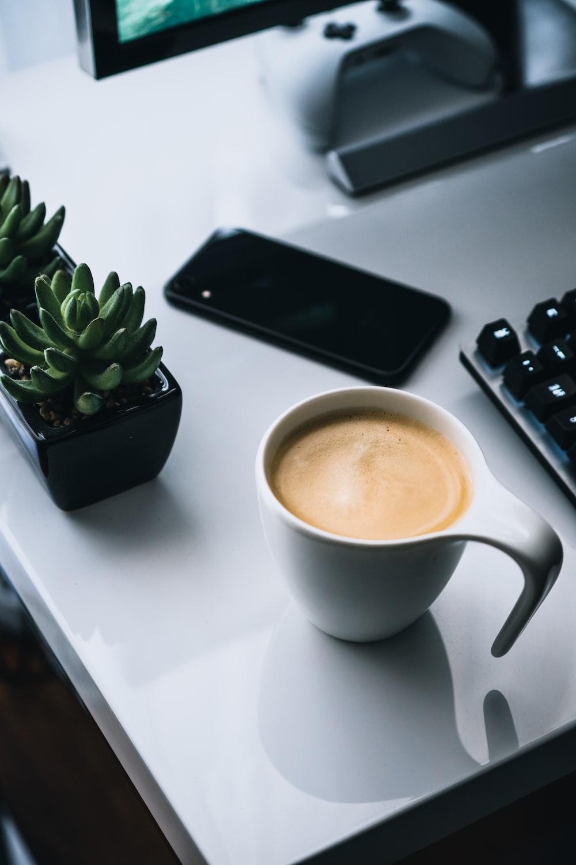 white ceramic mug beside black iphone 4