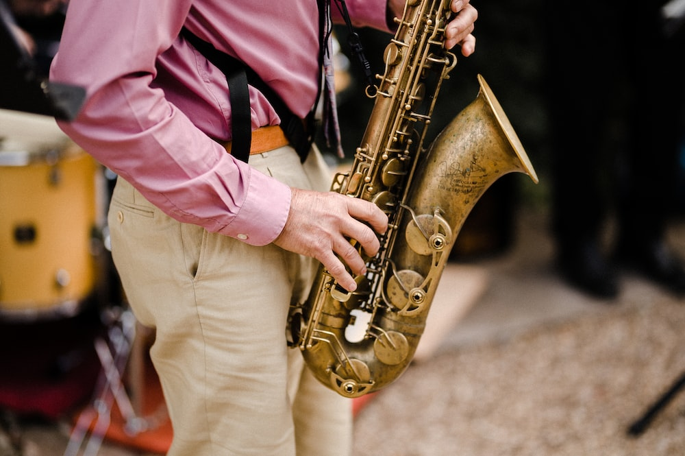 person in pink dress shirt playing saxophone