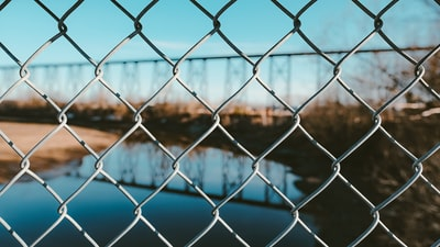 grey metal fence with chain link fence