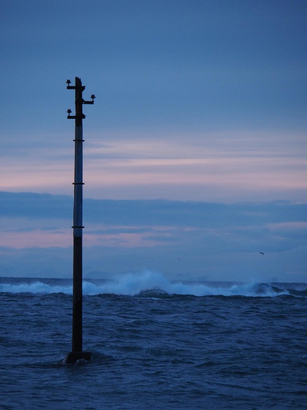 black metal post near sea during daytime