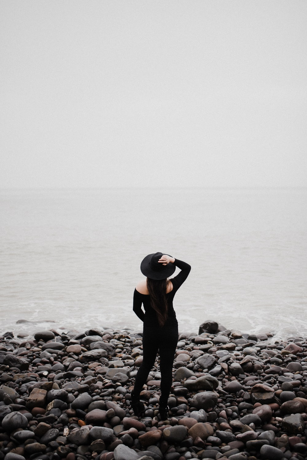 woman in black long sleeve shirt and black pants standing on rocky shore during daytime
