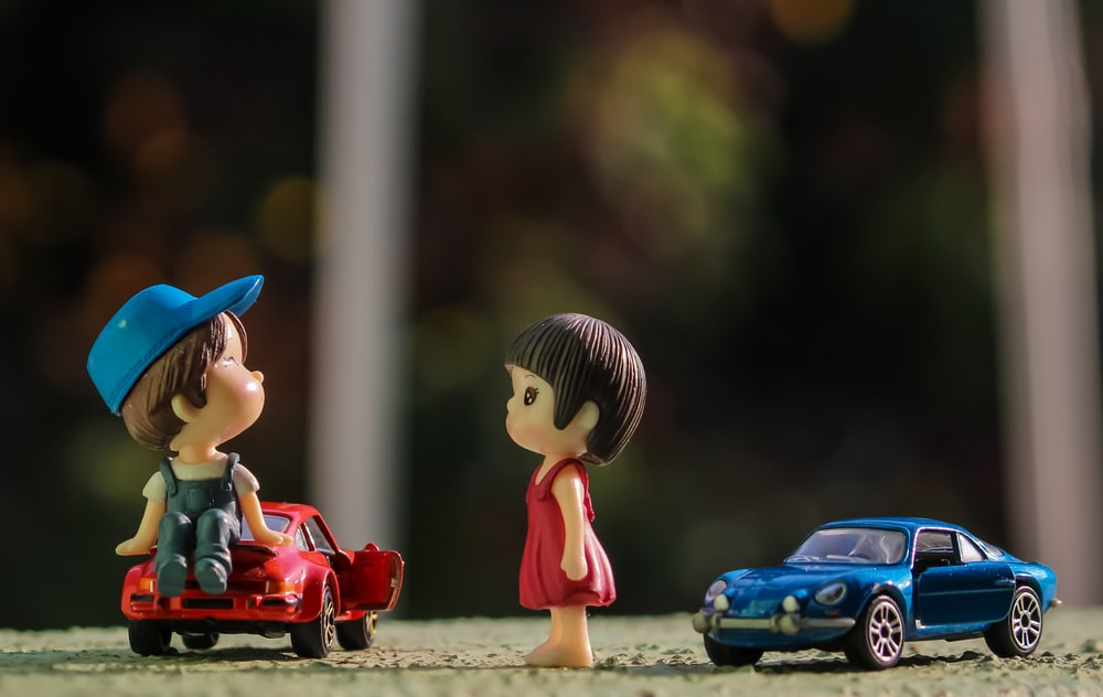 boy in red shirt and blue hat holding red car toy