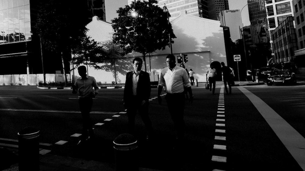 grayscale photo of people walking on pedestrian lane