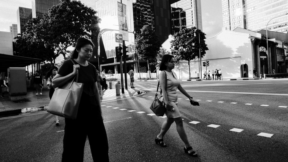 man and woman walking on the street in grayscale photography