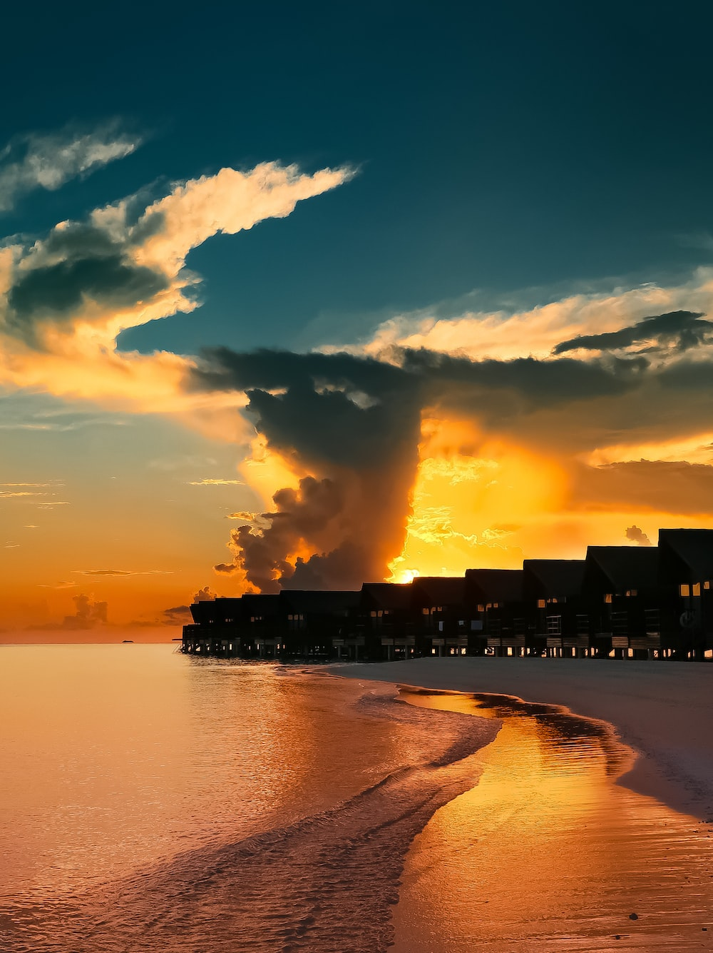silhouette of building near sea during sunset