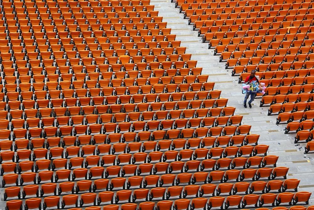 people walking on orange and white stadium