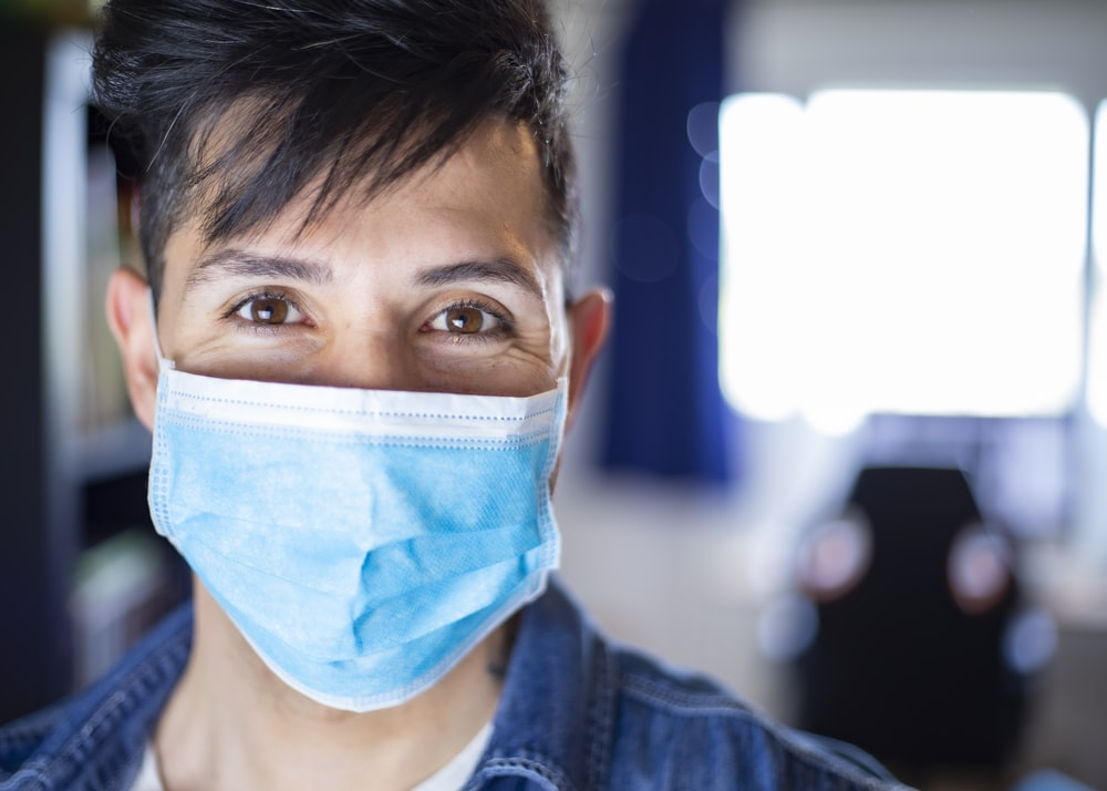 woman in blue denim jacket with white face mask