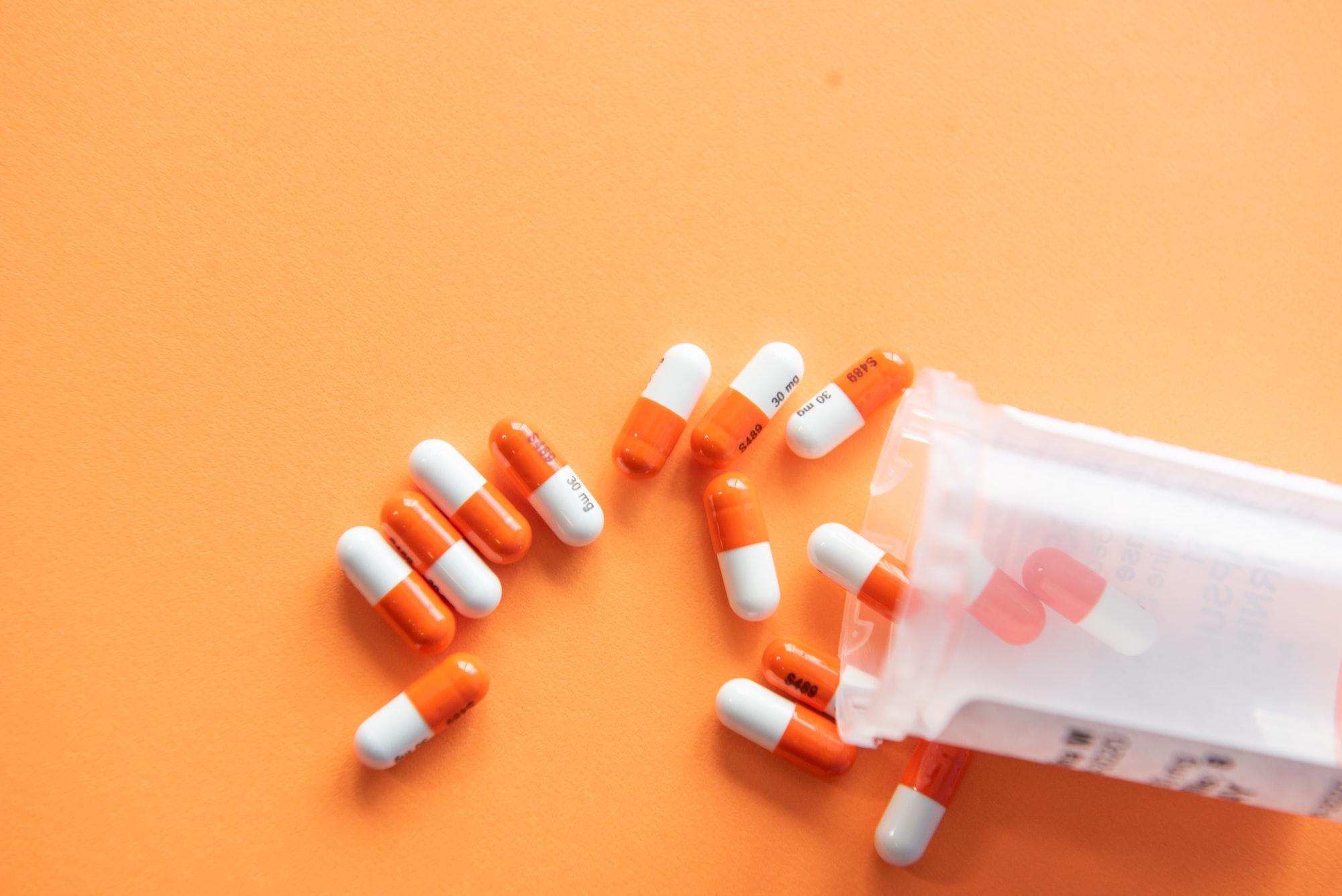 Prescription drugs on an orange background with a pill bottle. Orange pills.